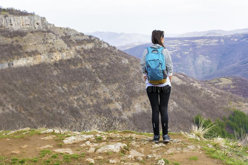 Hiker Woman Looking the Mountain View. Happy woman relaxing in a high mountain and Enjoying the Panoramic View from above .Adventure Concept stock photos