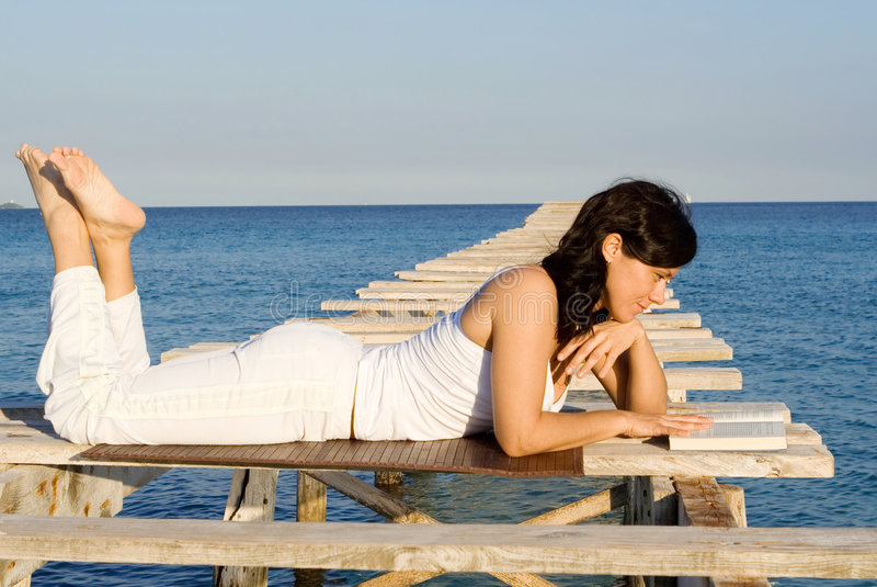 Happy woman relaxing reading stock photos