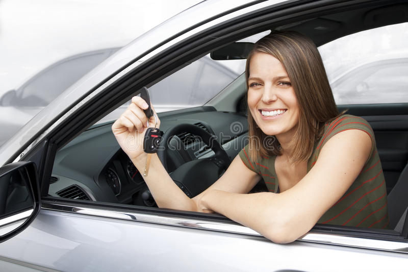 Happy Woman Renting a Car. A beautiful, smiling woman holding the keys to a new car or new rental royalty free stock photography