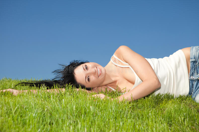 Happy woman rest on the green grass stock images