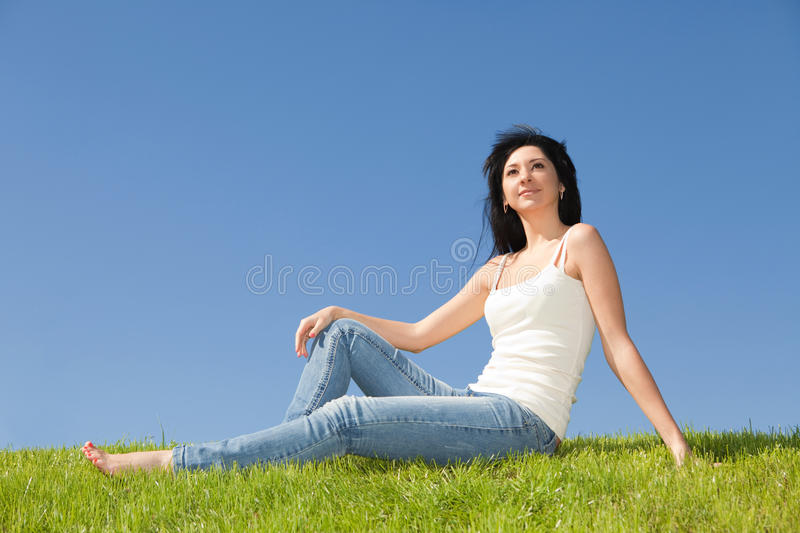 Happy woman rest on the green grass royalty free stock photography