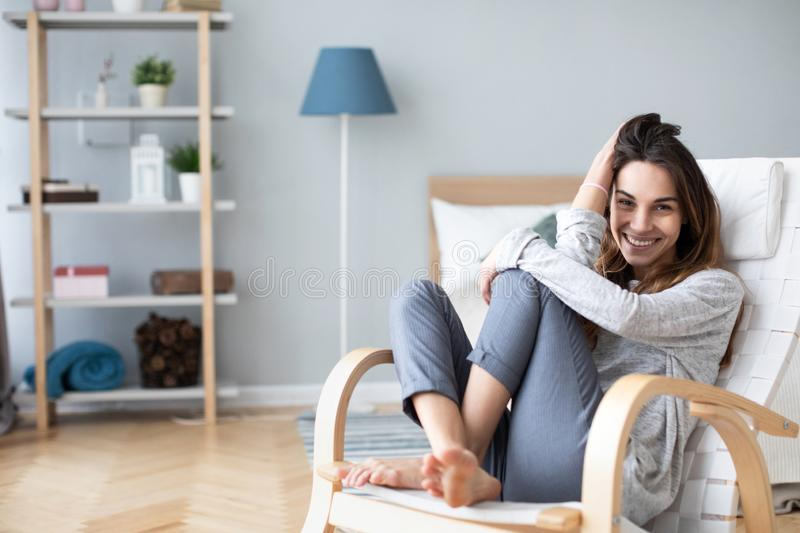 Happy woman resting comfortably sitting on modern chair in the living room at home royalty free stock photography