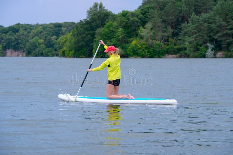 Happy woman resting on the SUP board and enjoying life in the early morning on the big river. Stand on the paddle boarding house royalty free stock photography