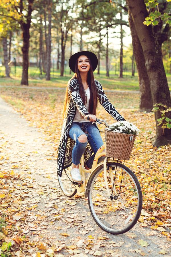Happy woman riding bike bicycle in fall autumn park stock image