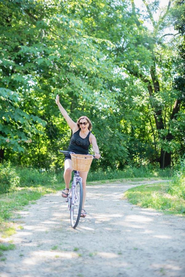 Happy woman riding bike reaching finish line stock photo