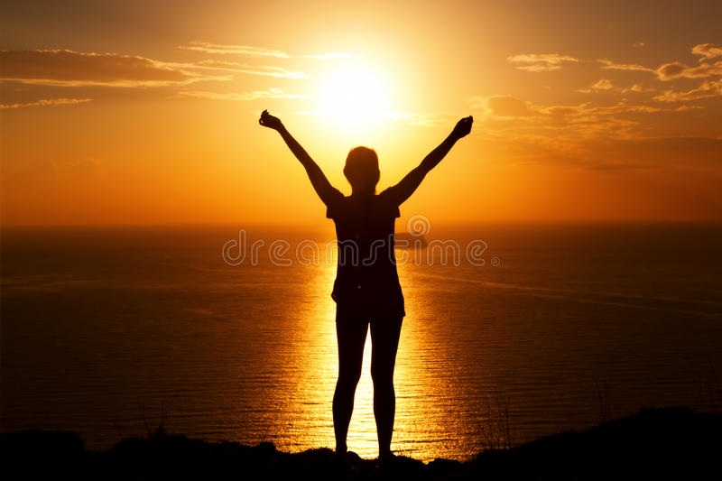 Happy woman on the rock with hands up. royalty free stock image
