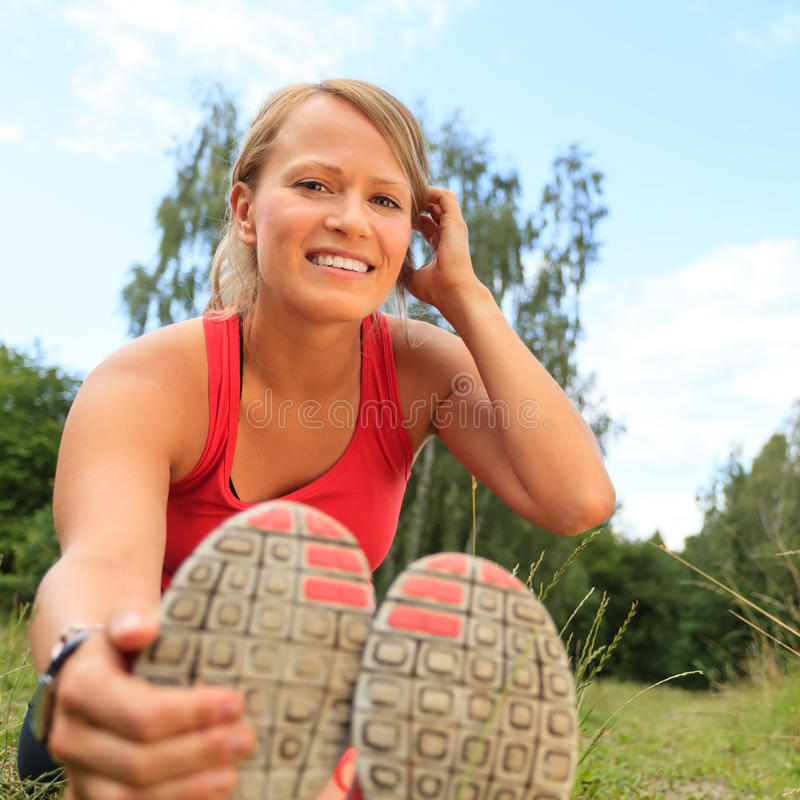 Happy Woman Runner Exercising and Stretching, summer nature outdoors royalty free stock photos