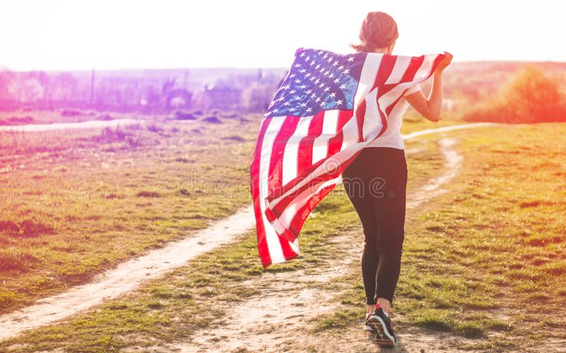 Women running in the field with American flag USA celebrate 4th of July. Happy woman running in the field with American flag USA celebrate 4th of July royalty free stock images