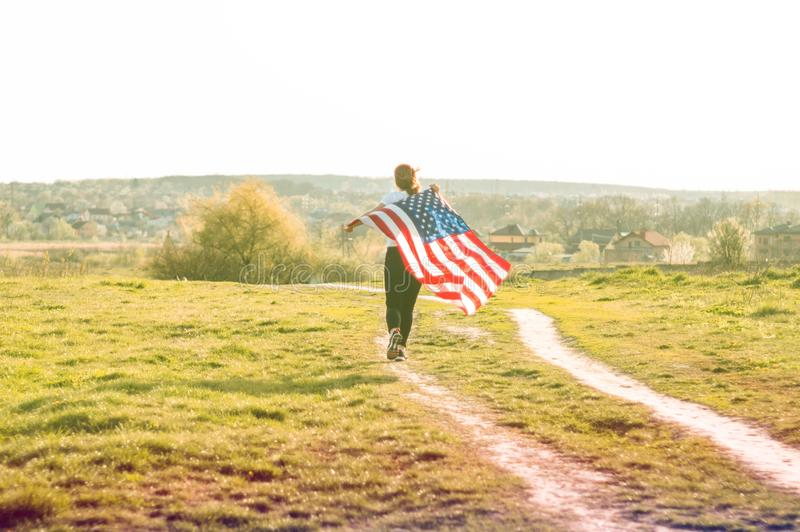 Women running in the field with American flag USA celebrate 4th of July. Happy woman running in the field with American flag USA celebrate 4th of July royalty free stock photography