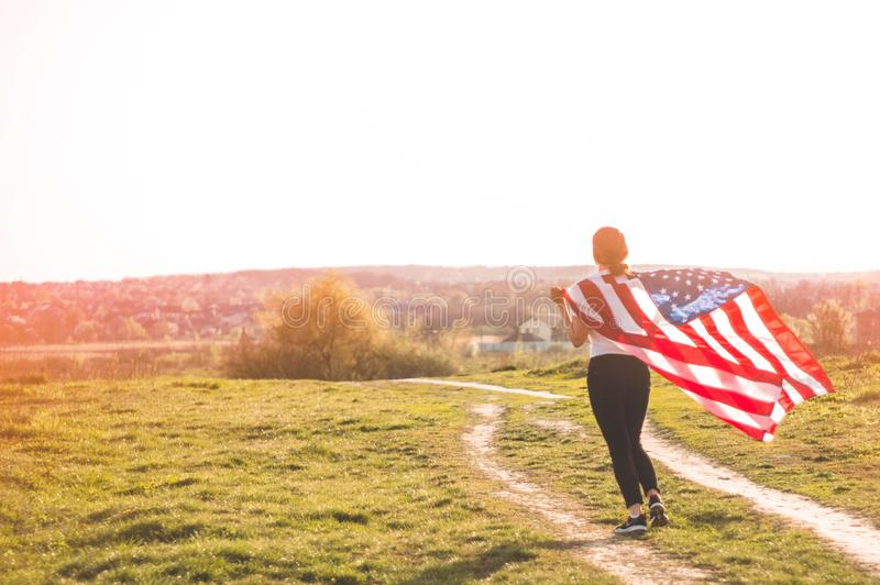 Women running in the field with American flag USA celebrate 4th of July. Happy woman running in the field with American flag USA celebrate 4th of July royalty free stock image