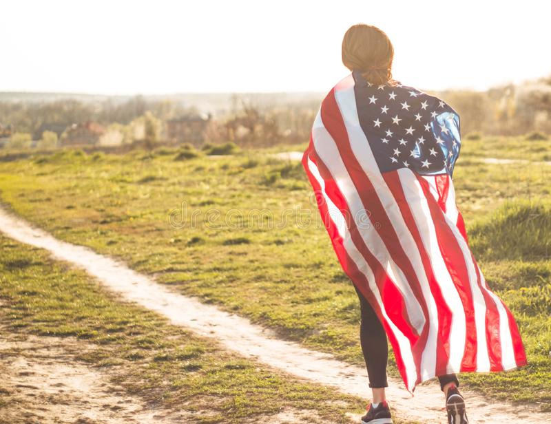 Women running in the field with American flag USA celebrate 4th of July. Happy woman running in the field with American flag USA celebrate 4th of July stock image