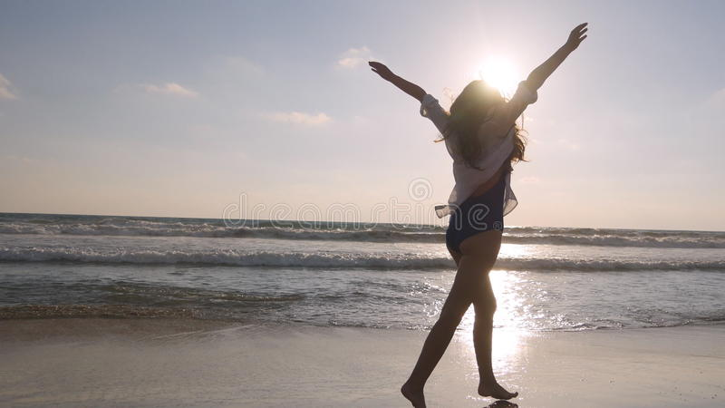 Happy woman running and spinning on the beach near the ocean. Young beautiful girl enjoying life and having fun at sea royalty free stock photos