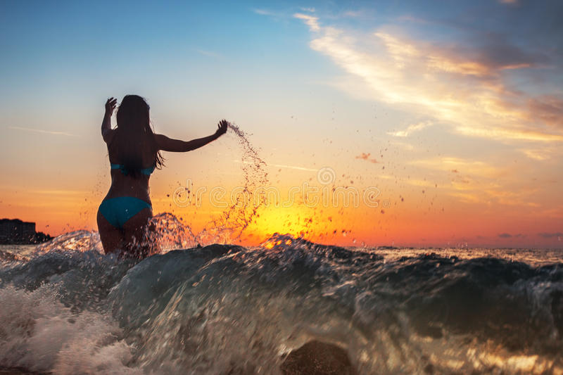 Happy woman running in the sunset on the beach stock image