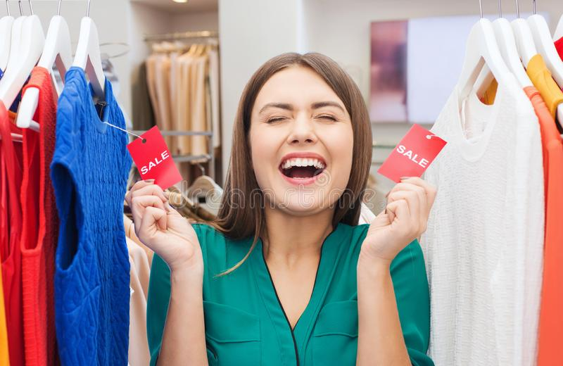 Happy woman with sale tags at clothing store. Sale, shopping and people concept - happy woman with tags on clothes over clothing store background royalty free stock image