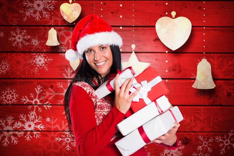 Happy woman in santa hat holding stack of christmas gifts stock photo