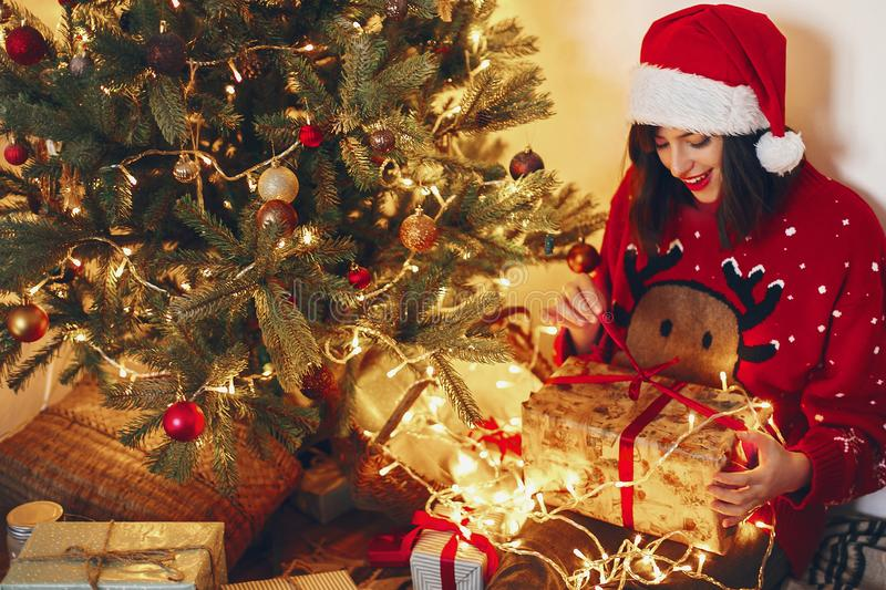 happy woman in santa hat opening gift box at christmas tree lights. space for text. merry christmas and happy new year concept. s stock photo