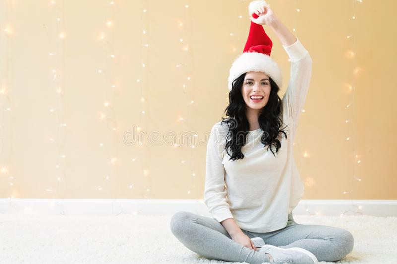 Happy woman with a Santa hat. On a shiny light background stock photography