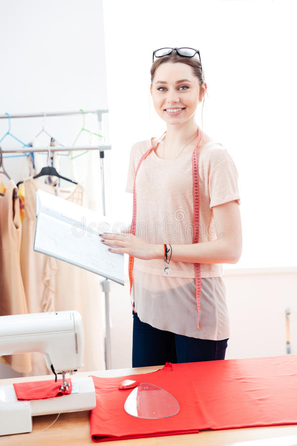 Happy woman seamstress standing and working with red fabric stock photography
