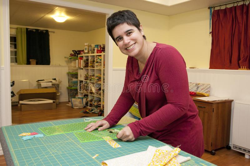 Happy woman in sewing room. Smiling person working with a fabric grid and cutter in their craft room stock image