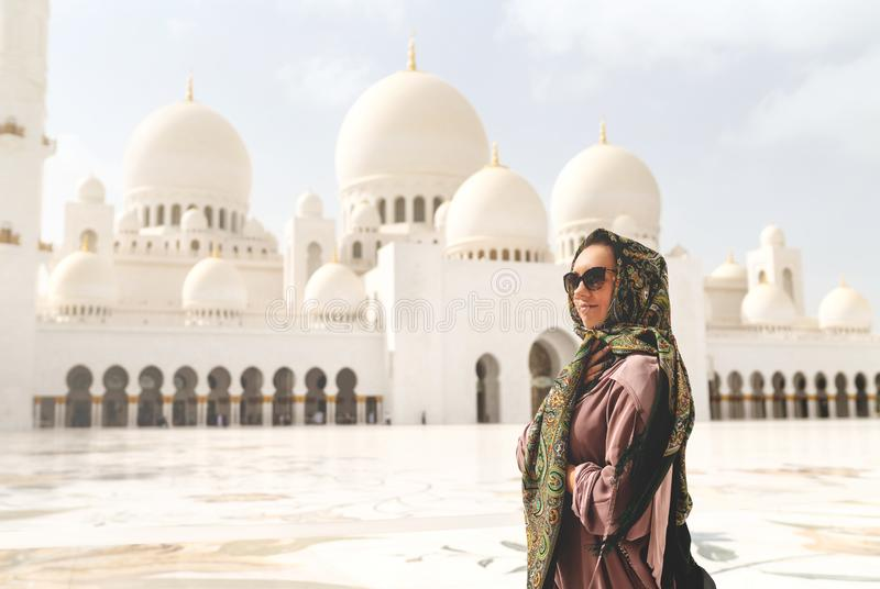 Happy woman in The Sheikh Zayed Grand Mosque. Female tourist with headscarf and dress in Adu Dhabi. stock photo