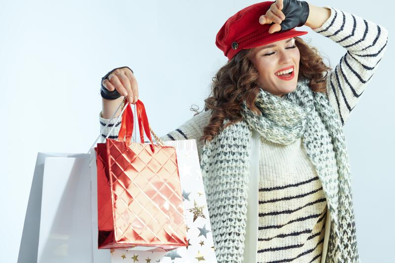 Happy woman shopper  on winter light blue background stock images