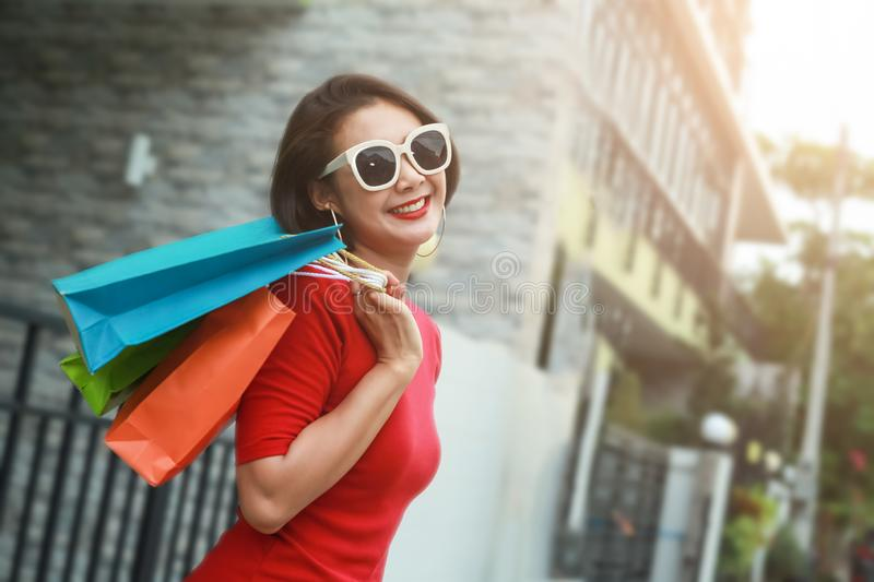 Happy woman with shopping bags enjoying in shopping outdoor stock photo