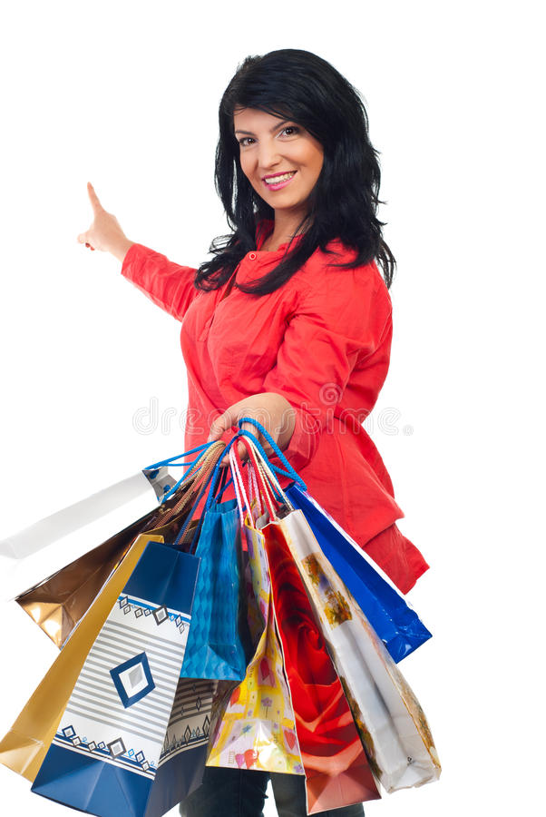 Happy woman with shopping bags pointing to copy stock photo