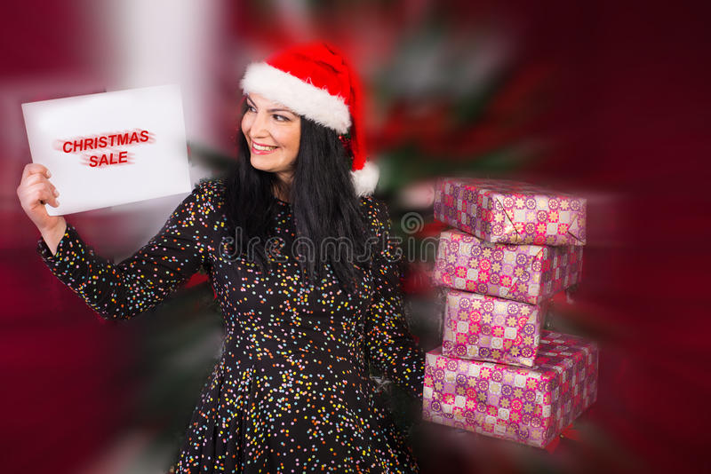 Happy woman shopping Christmas gifts. Happy woman buying Christmas gifts and holding paper with written Christmas sale in front of blurred motion background of royalty free stock photography