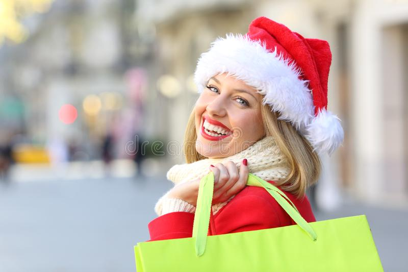 Happy woman shopping in christmas looking at you. Portrait of a happy woman weating a santa claus hat shopping in christmas looking at you outdoors on the street stock photo