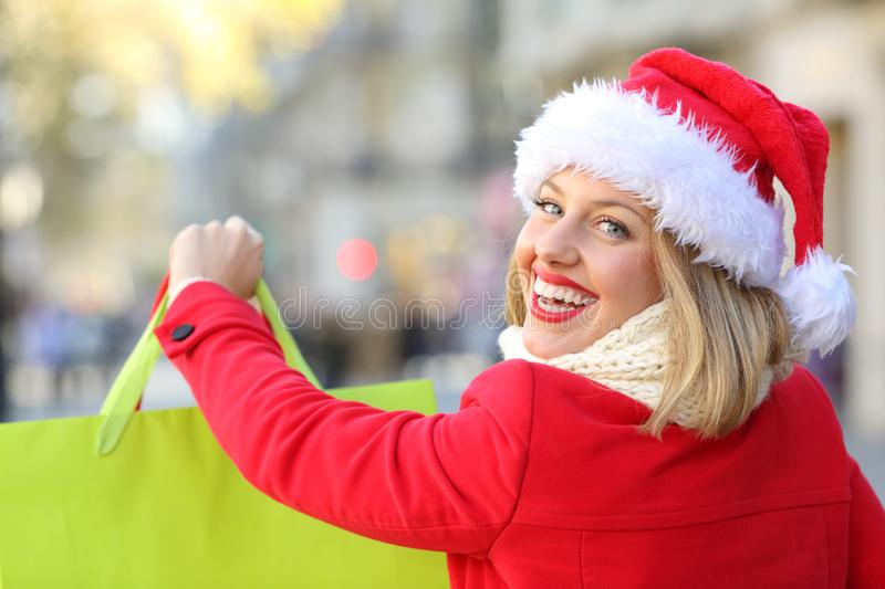 Happy woman shopping in christmas. Portrait of a happy woman shopping in christmas wearing a santa claus hat outdoors on the street royalty free stock photography
