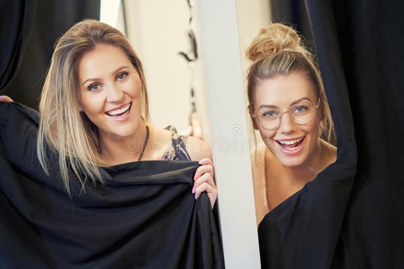 Happy woman shopping for clothes in store. Picture of happy women shopping for clothes in store stock image