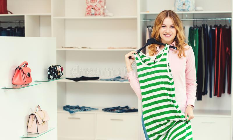 Happy woman shopping in clothing store. Sale, fashion, consumerism and people concept. Young woman choosing clothes in mall. Shopp stock photos