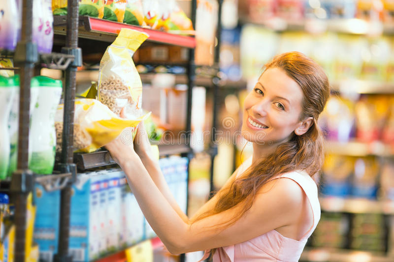 Happy woman shopping in a grocery store royalty free stock images