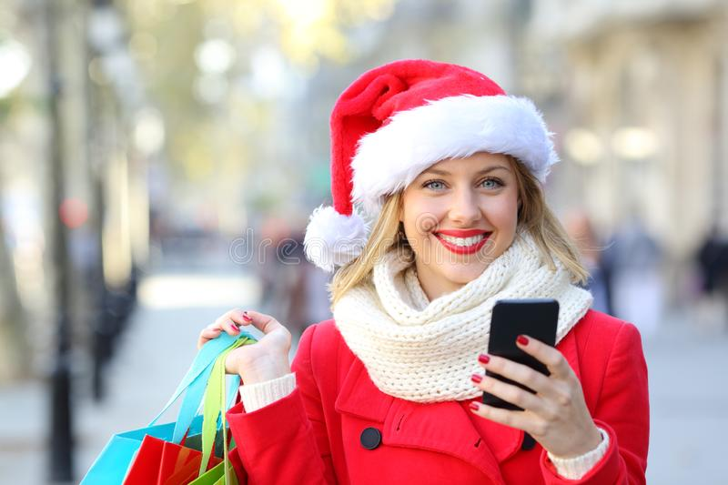 Happy woman shopping online on christmas holidays. Front view portrait of a happy shopper shopping online looking at camera on christmas holidays on the street stock photography