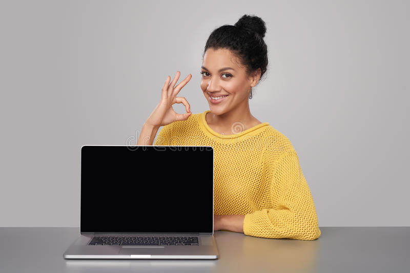 Happy woman showing blank black comuter screen. Happy mixed race african american - caucasian woman showing blank black laptop computer screen, looking at camera royalty free stock image