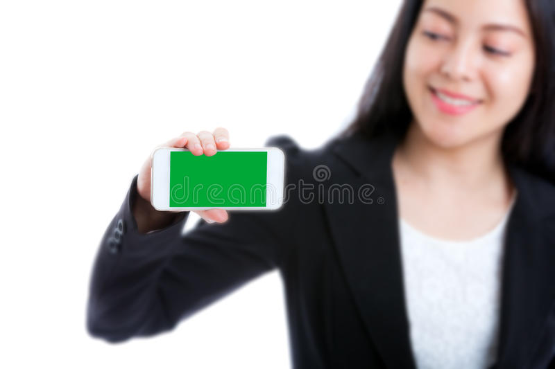 Happy woman showing blank smart phone green screen on white back stock image