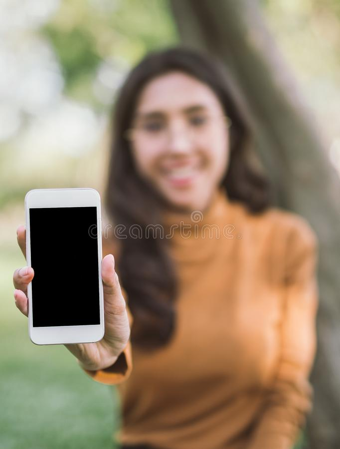 Happy woman showing blank smart phone.screen over park background. Focus on smartphone royalty free stock images