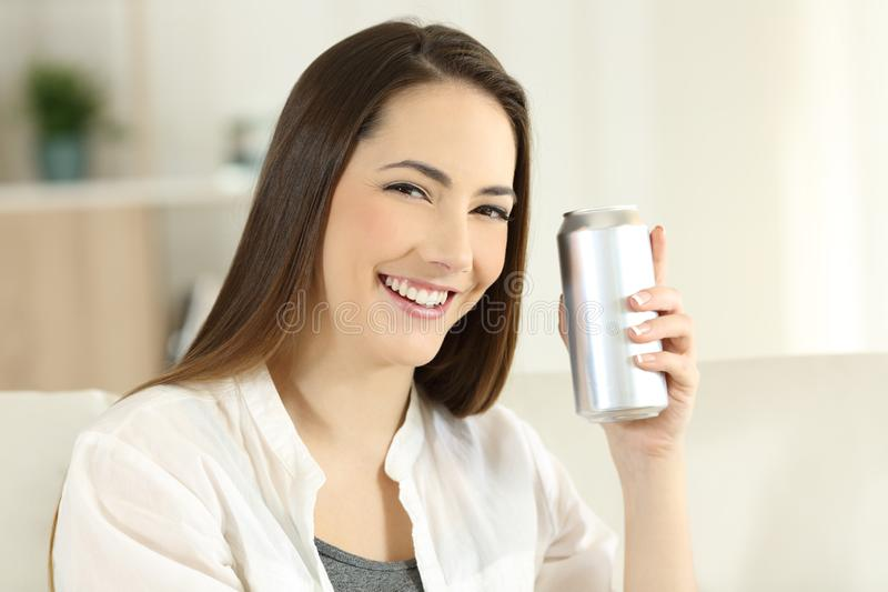 Woman showing a refreshment can at home. Happy woman showing a refreshment can sitting on a couch in the living room at home stock images
