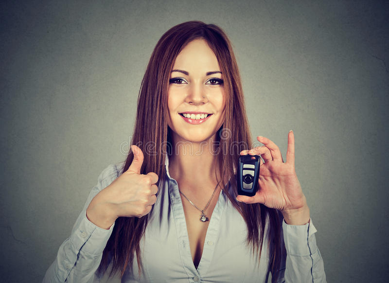 Happy woman showing remote car keys and thumbs up. Woman showing remote car keys and thumbs up on gray wall background royalty free stock photo