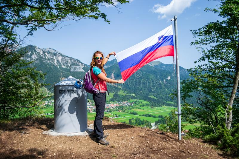 Happy woman showing the Slovenian flag after finishing climbing the via ferrata route on the Grancisce hill, above Mojstrana stock image