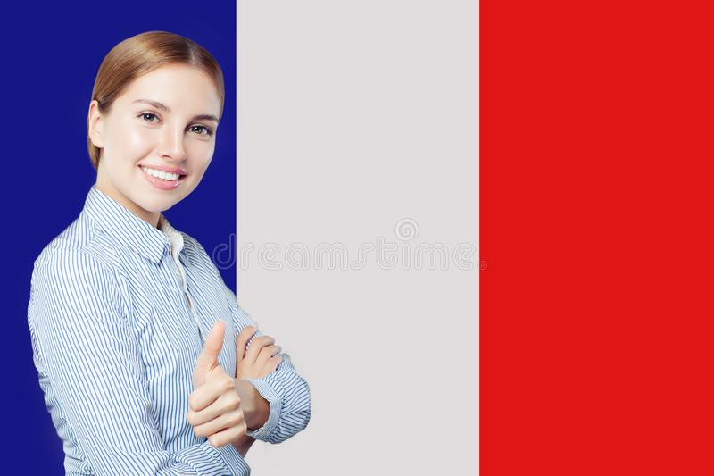 Happy woman showing thumb up on French flag background. royalty free stock image