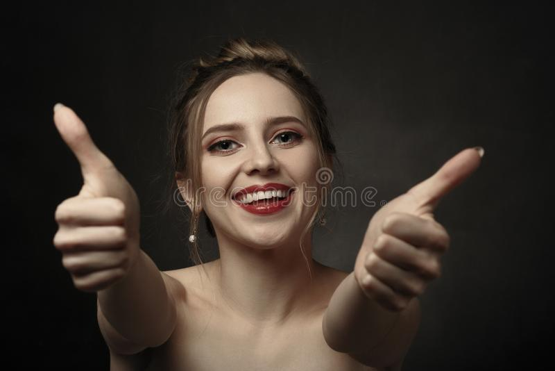 Woman show thumbs. Happy woman shows her thumbs on black background looking at camera laughing royalty free stock image