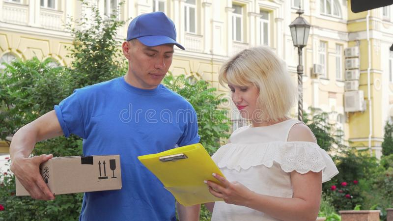 Happy woman signing receipt and receiving a package from courier stock image