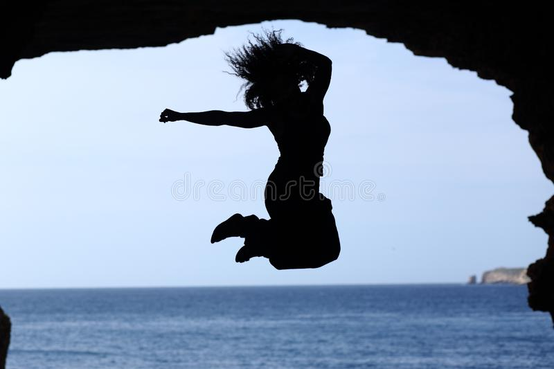 Happy woman silhouette jumping on the beach stock photos