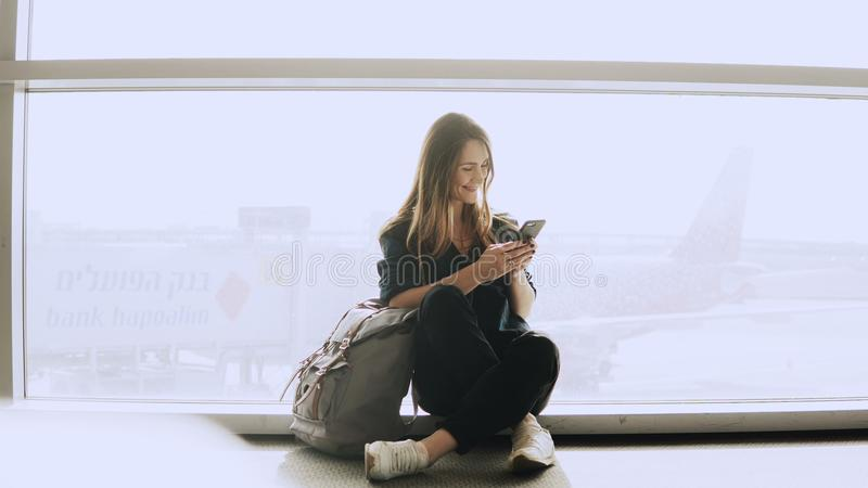Happy woman sits with smartphone by airport window. Caucasian girl with backpack using messenger app in terminal. 4K. royalty free stock photo