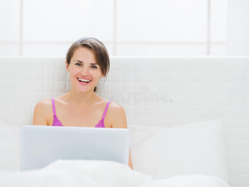 Download Happy Woman Sitting On Bed And Working On Laptop Stock Image - Image: 26805731