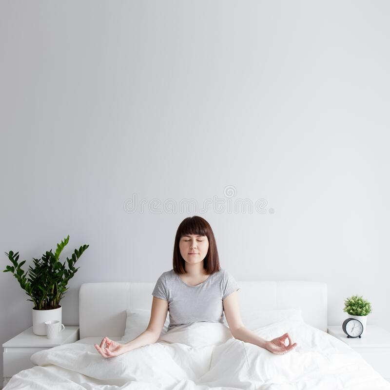 Happy woman sitting on bed in yoga pose at home, copy space over white wall royalty free stock photo