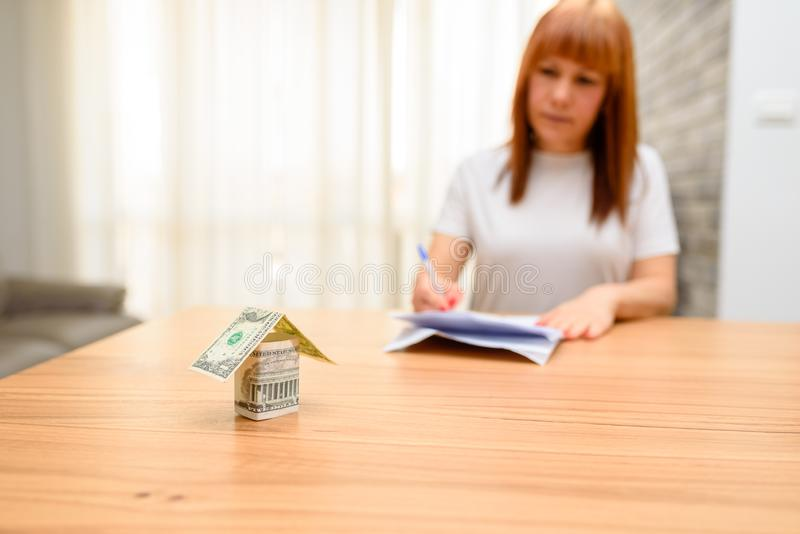 Happy woman sitting and calculating bills in the home office.Money house from dollar banknote on wooden table. royalty free stock images