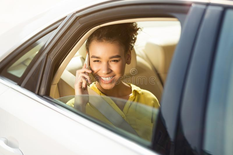 Happy woman sitting in car and talking on phone stock image