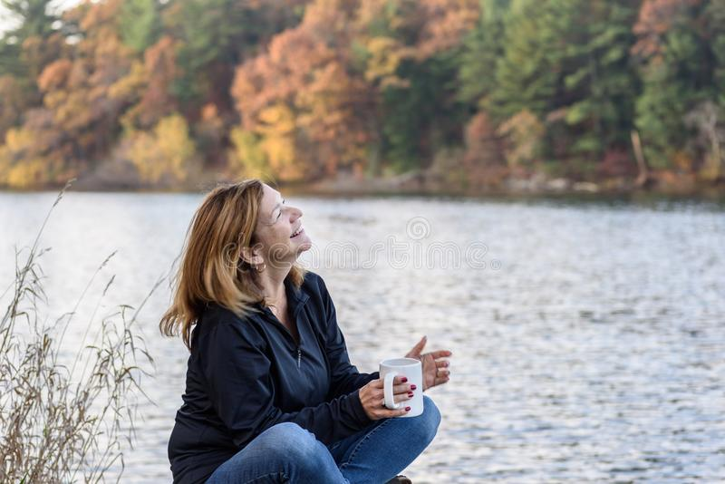 woman holding cup of coffee laughing along lakefront with colorful fall trees in background royalty free stock photos